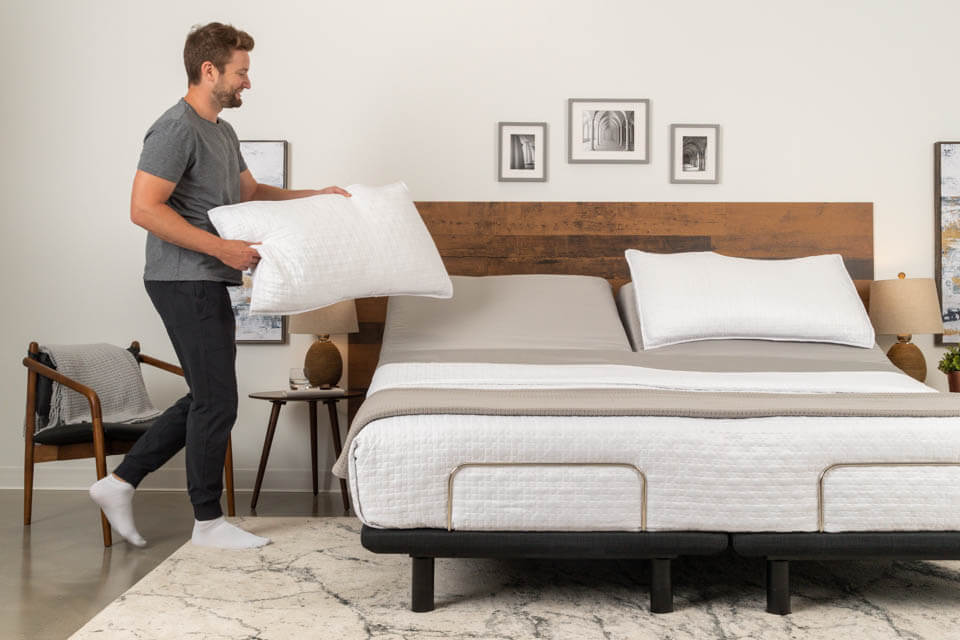 Podium Adjustable Bed Base Man Adding Pillow | Podiumbed.ca